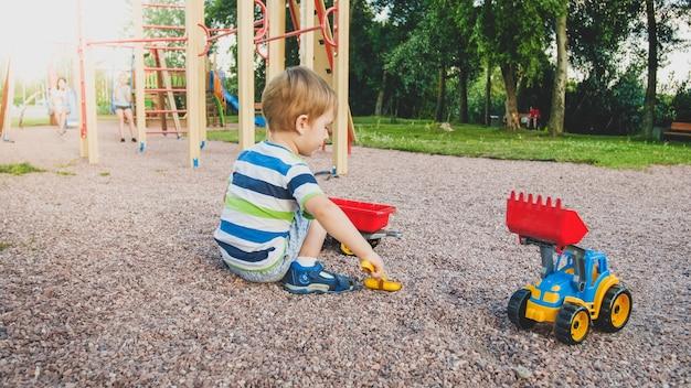 Nahaufnahmebild des netten kleinen jungen, der auf dem spielplatz mit spielwaren spielt. kind hat spaß mit lkw, bagger und anhänger. er gibt vor, ein baumeister oder fahrer zu sein Premium Fotos
