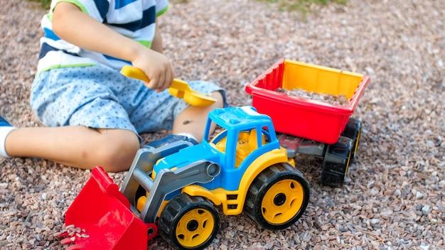 Nahaufnahmebild des netten kleinen jungen, der auf dem spielplatz mit spielwaren spielt. kind hat spaß mit lkw, bagger und anhänger. er gibt vor, ein baumeister oder fahrer zu sein