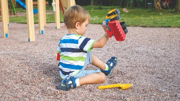 Nahaufnahmebild des netten kleinen jungen, der auf dem spielplatz mit spielwaren spielt. kind hat spaß mit lkw, bagger und anhänger