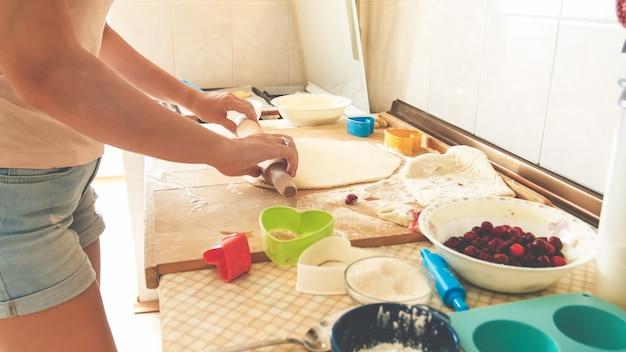 Nahaufnahmebild des rollenteigs der jungen frau mit hölzernem nudelholz. hausfrau macht pizza zu hause in der küche