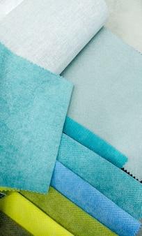 Nahaufnahmebild des sortiments von stoffproben für weiche möbel. blaue und grüne materialstücke. abstrakter nahaufnahmehintergrund