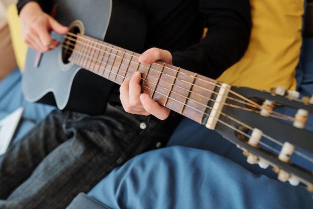 Nahaufnahmebild des teenagers, der gitarre spielt und lied zu hause singt
