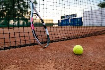 Nahaufnahmebild des Tennisschlägers und -balls auf dem Sandplatz. Blick durchs Netz.