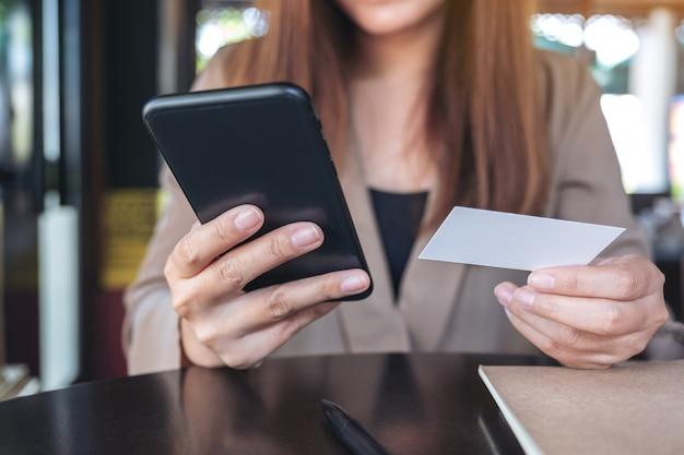 Nahaufnahmebild einer asiatischen frau, die ein schwarzes smartphone und eine visitenkarte im café hält