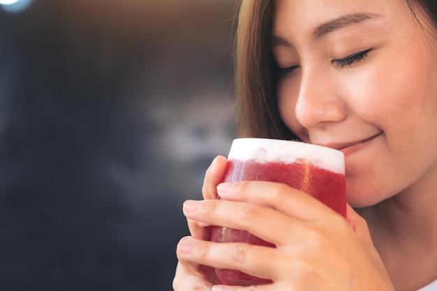 Nahaufnahmebild einer asiatischen frau genießen, erdbeersoda mit dem fühlen glücklich zu trinken