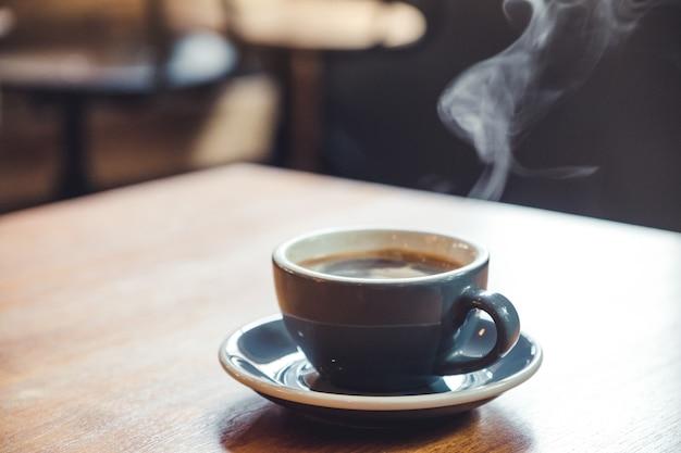 Nahaufnahmebild einer blauen tasse heißen kaffees mit rauch auf weinlese-holztisch im café
