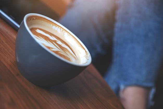 Nahaufnahmebild einer blauen tasse heißen lattekaffees auf holztisch mit frau, die im café sitzt