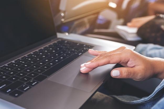 Nahaufnahmebild einer frau, die am laptop-computer-touchpad beim sitzen in der kabine verwendet und berührt