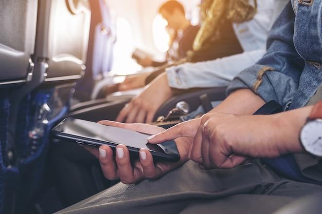 Nahaufnahmebild einer frau, die an einem schwarzen smartphonebildschirm hält und berührt, während sie in der kabine sitzt