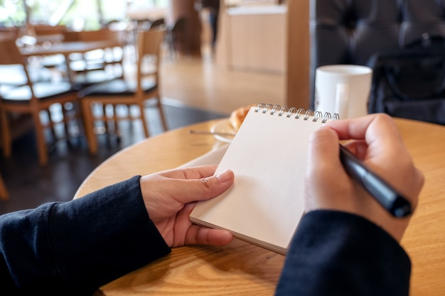 Nahaufnahmebild einer frau, die auf leerem notizbuch mit croissant in einem teller auf tisch im café hält und schreibt