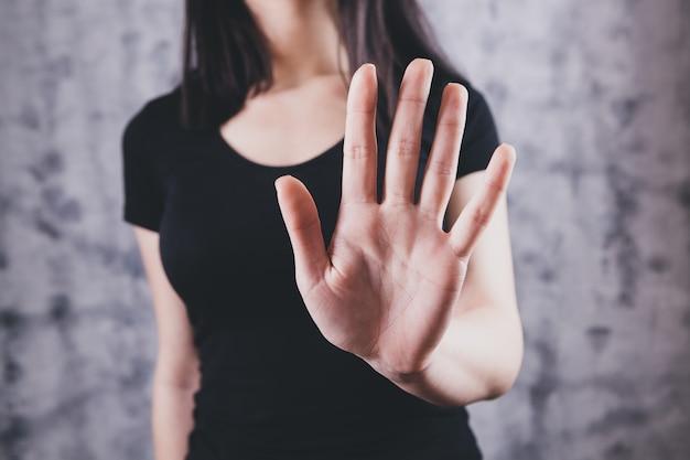 Nahaufnahmebild einer frau, die ausgestreckte hand und stopphandzeichen zeigt