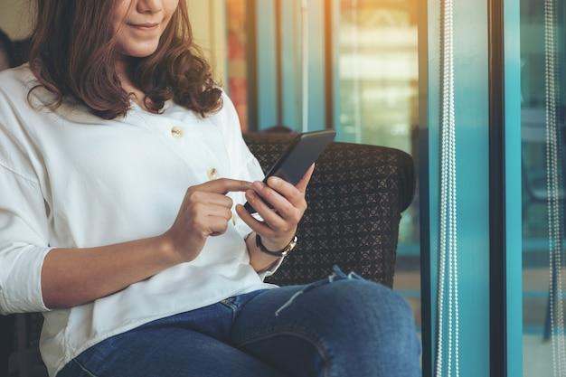 Nahaufnahmebild einer frau, die das smartphone im café hält, verwendet und zeigt