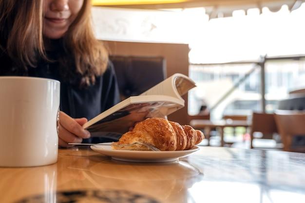 Nahaufnahmebild einer frau, die ein buch mit einem stück croissant in einem teller und einer tasse kaffee auf holztisch hält und liest