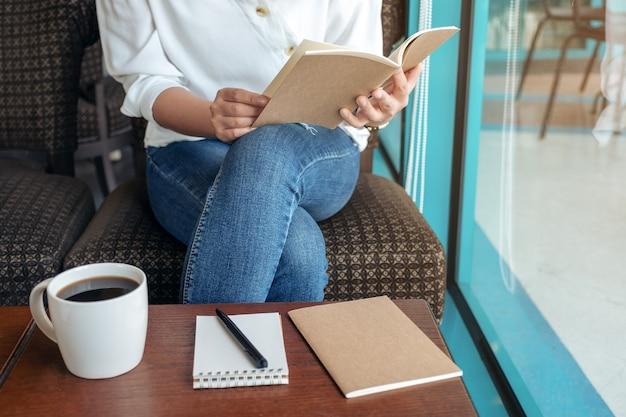 Nahaufnahmebild einer frau, die ein buch öffnet, um mit notizbüchern und kaffeetasse auf holztisch im café zu lesen