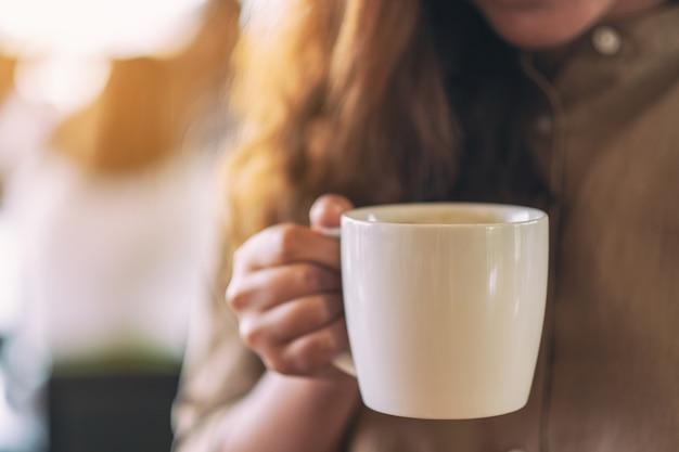Nahaufnahmebild einer frau, die eine weiße tasse heißen kaffees hält