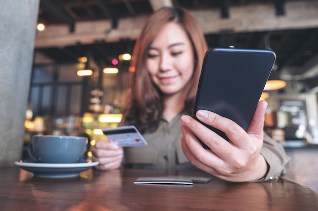 Nahaufnahmebild einer frau, die kreditkarte hält und mobile banking beim sitzen im café verwendet