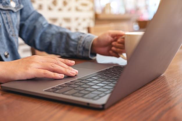 Nahaufnahmebild einer frau, die laptop-touchpad auf holztisch beim trinken von kaffee verwendet und berührt