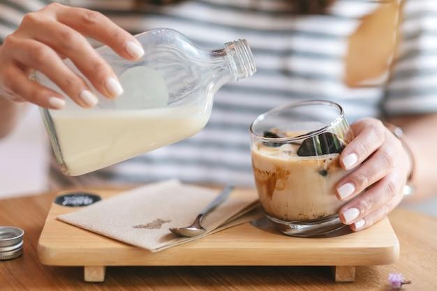 Nahaufnahmebild einer frau, die milch in ein glas eiswürfelkaffee im café gießt