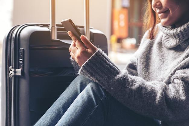 Nahaufnahmebild einer frau, die sitzt und handy mit einem schwarzen gepäck für das reisen verwendet