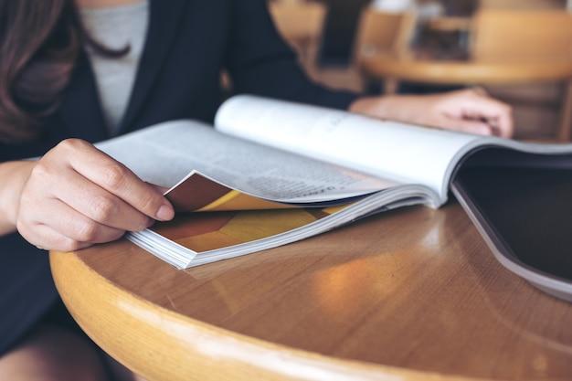 Nahaufnahmebild einer geschäftsfrau, die ein buch im modernen café liest