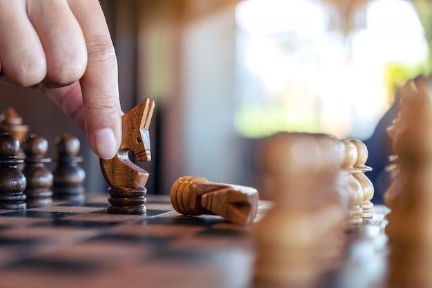 Nahaufnahmebild einer hand, die ein pferd hält und bewegt, um ein anderes pferd im hölzernen schachbrettspiel zu gewinnen