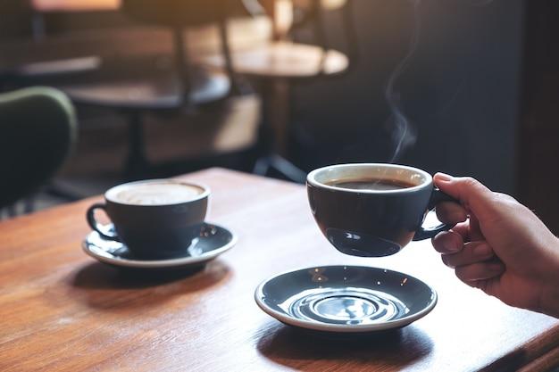 Nahaufnahmebild einer hand, die eine blaue tasse heißen kaffees mit rauch auf holztisch im café hält