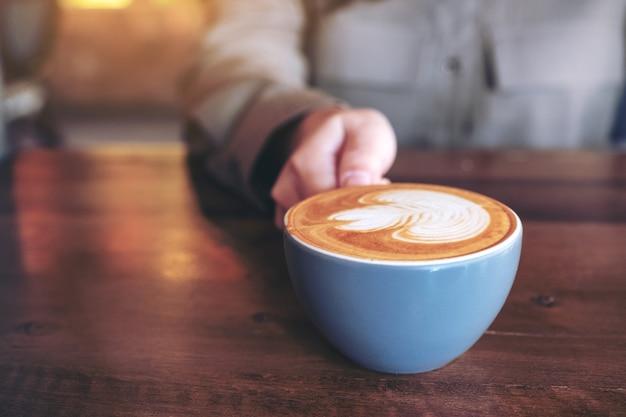 Nahaufnahmebild einer hand, die eine blaue tasse heißen latte-kaffees mit latte-kunst auf holztisch im café hält
