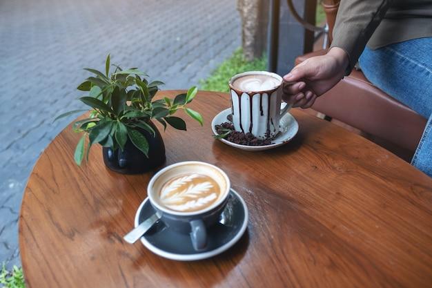 Nahaufnahmebild einer hand, die eine tasse heiße schokolade mit einer anderen tasse kaffee auf holztisch im café hält
