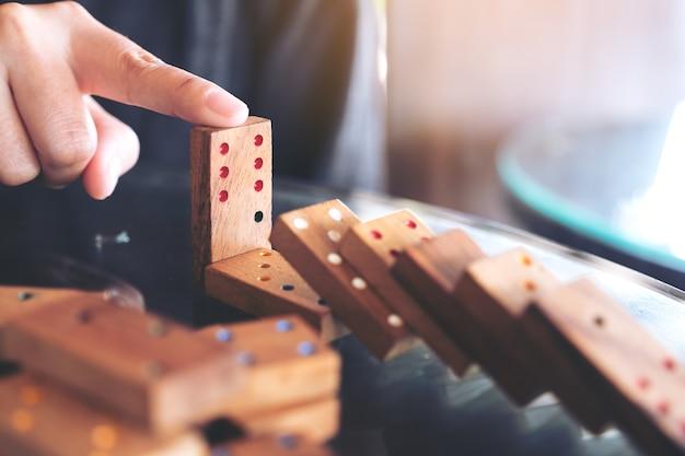 Nahaufnahmebild einer hand, die versucht, hölzernes dominospiel vom fallen auf tabelle zu stoppen