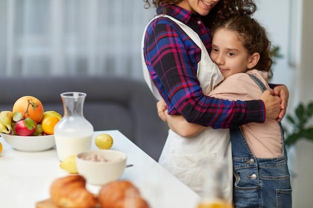 Nahaufnahmebild einer mutter umarmen ihre süße tochter in der küche am tisch, frühstücken zusammen.