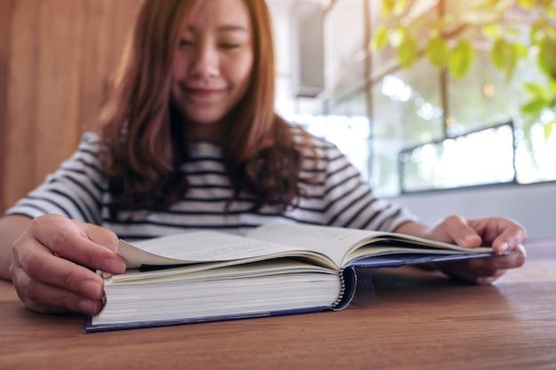 Nahaufnahmebild einer schönen asiatischen frau, die ein buch hält und liest