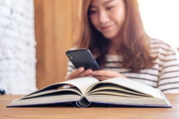 Nahaufnahmebild einer schönen asiatischen frau, die smartphone mit einem buch auf holztisch hält, benutzt und betrachtet
