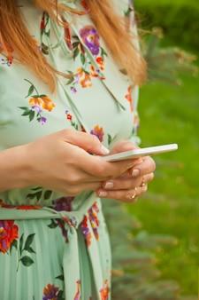 Nahaufnahmebild einer schönheit in einem blumenkleid, das intelligentes telefon auf der natur hält, verwendet und betrachtet