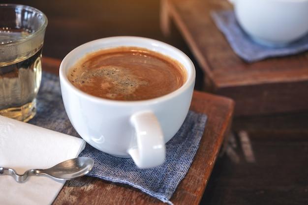 Nahaufnahmebild einer weißen tasse heißen kaffees und eines glases tee auf weinlese-holztisch im café