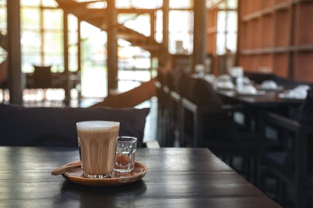Nahaufnahmebild eines glases des heißen kaffees auf holztisch im café