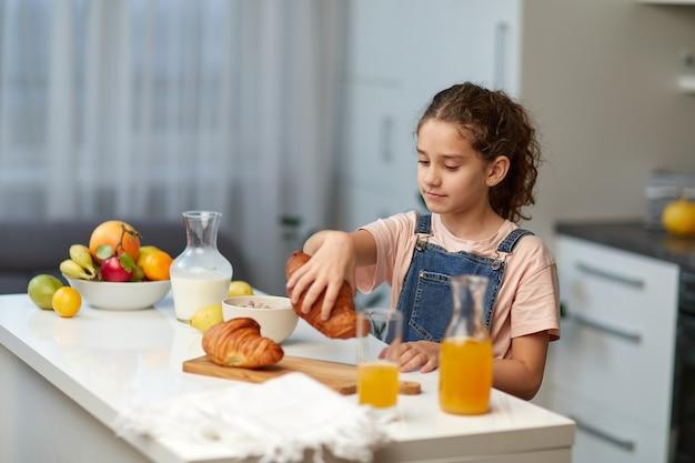 Nahaufnahmebild eines kleinen gelockten mädchens stehen ohrtisch und nehmen ein croissant in der küche.
