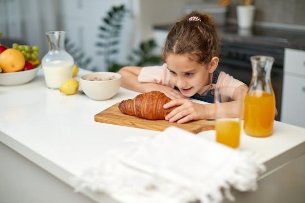 Nahaufnahmebild eines kleinen lockigen mädchens möchte croissant am tisch in der küche nehmen.