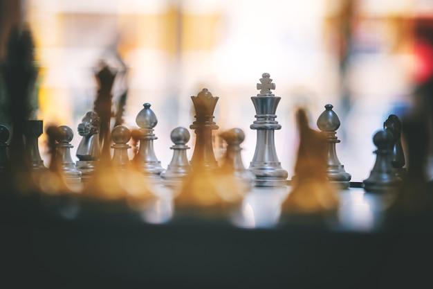 Nahaufnahmebild eines silbernen und goldenen farbschachspiels auf schachbrett