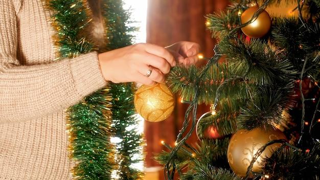 Nahaufnahmebild junge frau, die goldene kugeln am weihnachtsbaum im wohnzimmer hängt