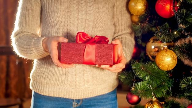 Nahaufnahmebild junge frau mit roter weihnachtsgeschenkbox mit großer schleife