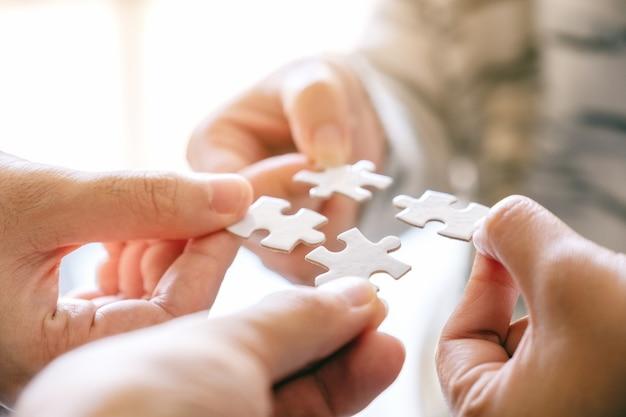 Nahaufnahmebild vieler leute, die ein weißes puzzleteil halten und zusammensetzen