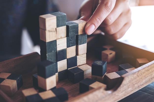 Nahaufnahmebild von den leuten, die hölzernes puzzlespielspiel spielen und aufbauen