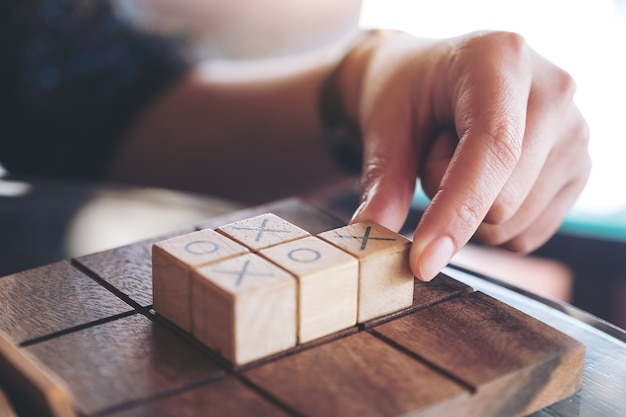 Nahaufnahmebild von den leuten, die hölzernes tic tac toe-spiel oder ox-spiel spielen