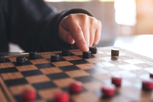 Nahaufnahmebild von den leuten, die kontrolleure in einem schachbrett spielen und sich bewegen