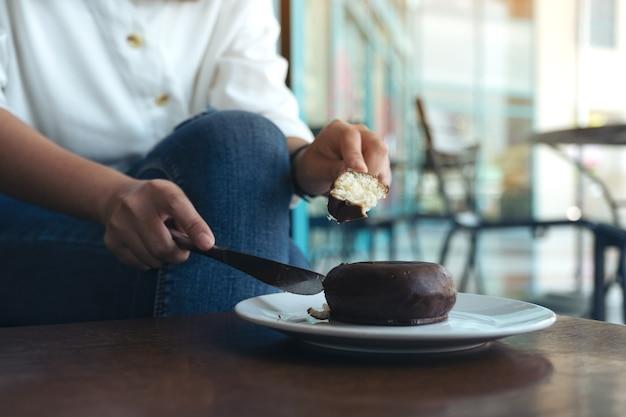 Nahaufnahmebild von frauenhänden, die ein stück schokoladendonut schneiden, um durch messer und gabel in einem weißen teller zu essen
