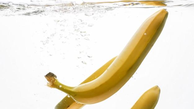 Nahaufnahmebild von frischen reifen bananen, die in wasser fallen und spritzen