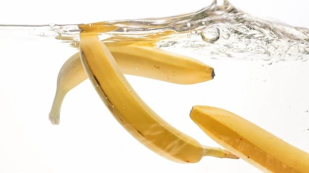 Nahaufnahmebild von frischen reifen bananen, die in wasser gegen weißen lokalisierten hintergrund fallen und spritzen