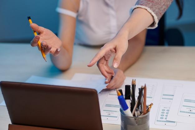 Nahaufnahmebild von geschäftsfrauen, die auf bildschirm des tablet-computers zeigen, wenn das layout der anwendungsschnittstelle mit dem ux-designer besprochen wird