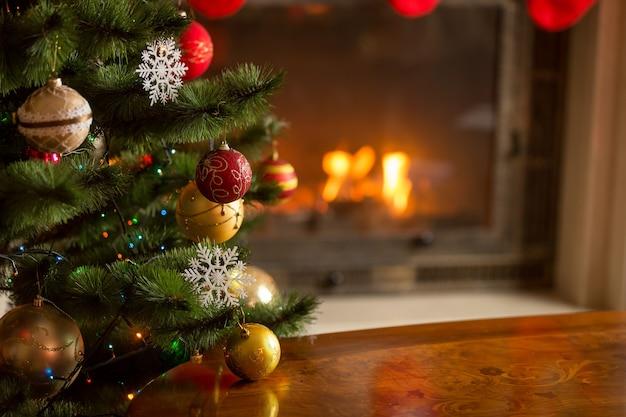 Nahaufnahmebild von goldenen und roten kugeln am weihnachtsbaum vor brennendem kamin. schöner weihnachtshintergrund