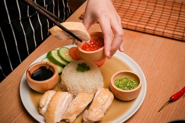 Nahaufnahmebild von hainan hühnchenreis weibliches eintauchen von hühnchen in chilisauce asiatisches leckeres essen
